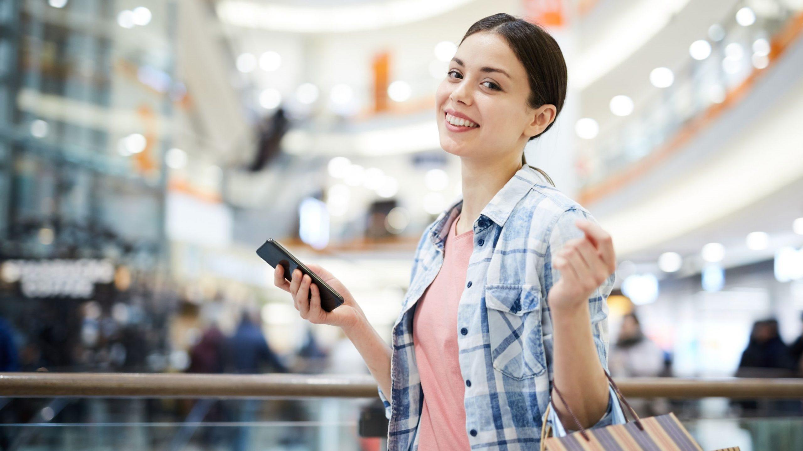 młoda uśmiechająca się kobieta z torbami na zakupy