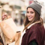 dwie uśmiechnięte kobiety trzymają torby z zakupami